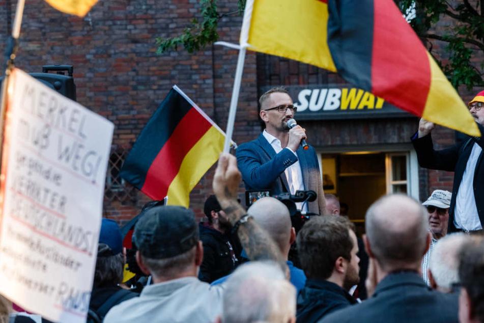 """Dennis Augustin, Kreisvorsitzender des AfD Landesverbandes Südwest-Mecklenburg, spricht vergangene Woche vor Teilnehmern der """"Merkel muss weg!""""-Kundgebung auf dem Gänsemarkt."""