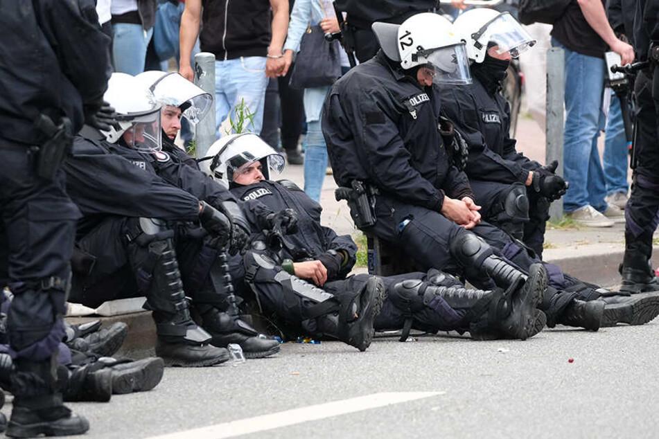 Völlig erschöpft sacken Polizisten zu Boden. Die tagelangen Ausschreitungen fordern ihren Tribut.