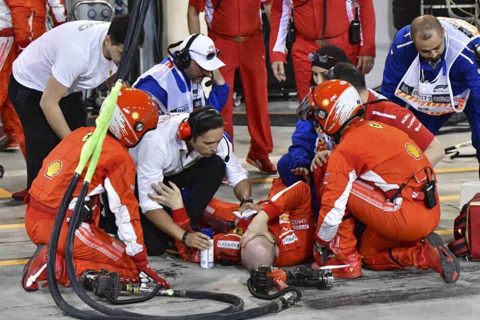 Nach dem Vorfall liegt der Mechaniker verletzt auf dem Boden, hält sich das Gesicht vor Schmerzen.