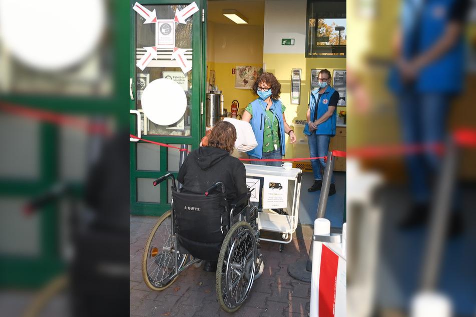 Ein Frau im Rollstuhl spricht mit Mitarbeitern der Bahnhofsmission am Berliner Ostbahnhof.