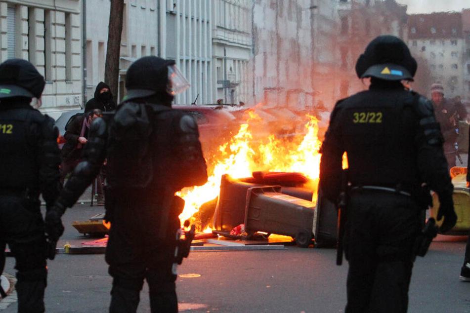 Polizisten stehen vor einer brennenden Barrikade und werden von Chaoten beworfen. Am Abend werden 69 Beamte verletzt sein.
