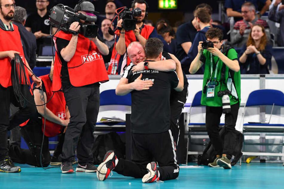 Trainer Alexander Waibl (mit dem Rücken im Bild) und Co-Trainer Wojciech Paleszniak fallen sich nach dem Matchball in die Arme.