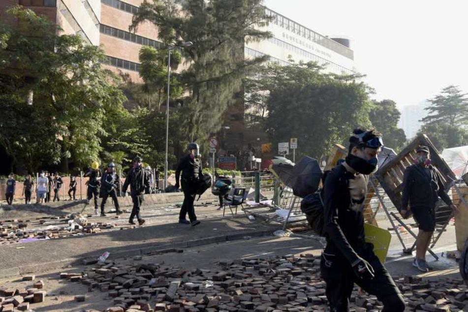 Demonstranten verlassen die Polytechnische Universität im Bezirk Kowloon nach heftigen Auseinandersetzungen mit der Polizei.