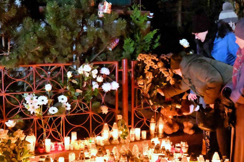 Blumen und Kerzen werden am Ort eines Brandes niedergelegt, bei dem fünf Mädchen gestorben sind.