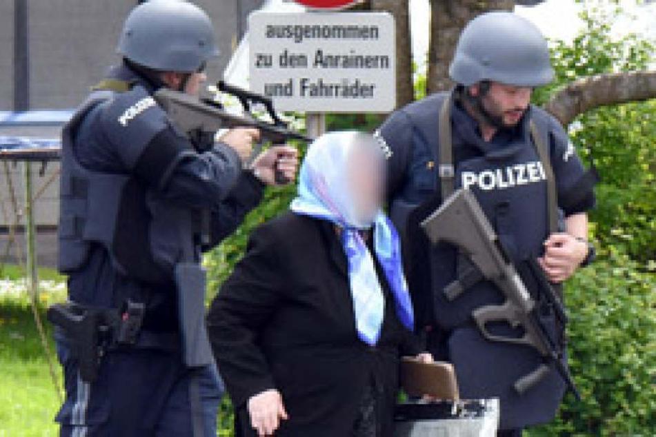 Beamte vor Ort bringen eine Frau in Sicherheit, die direkt am Tatort unterwegs war.