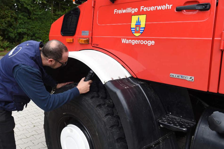 Ein Mitarbeiter überprüft das Feuerwehrfahrzeug.