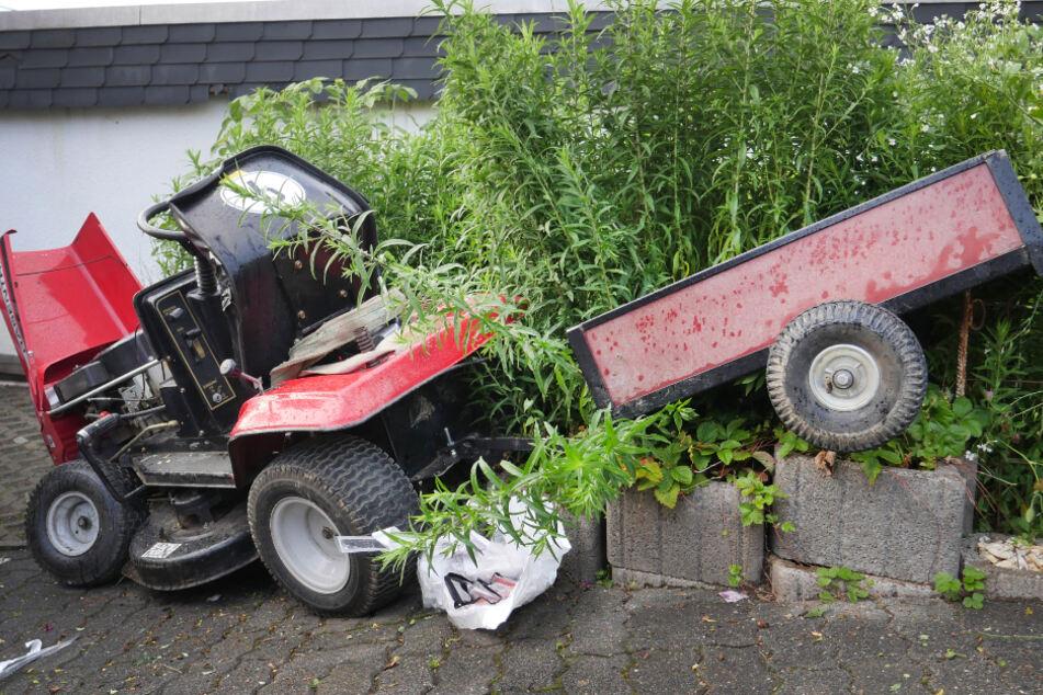 Ein Rasenmäher-Traktor steht nach einem Unfall an einer Hecke.