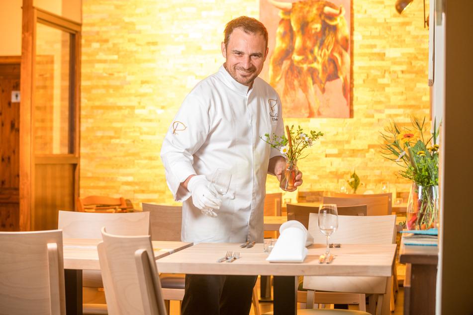 """Daniel Fischer schmückt für seine ersten Gäste im """"Daniels"""" die Tische mit frischen Blumen."""