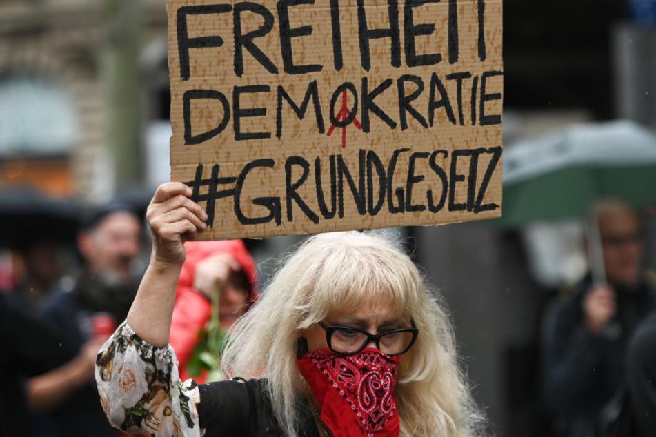 """Eine Frau hält während eines Protestzuges durch die Frankfurter Innenstadt ein Plakat mit der Aufschrift """"Freiheit Demokratie #Grundgesetz"""" hoch."""