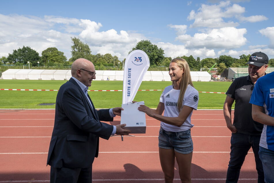 Sprinterin Corinna Schwab (22) nimmt das Geschenk vom Chemnitzer Stadtoberhaupt entgegen.