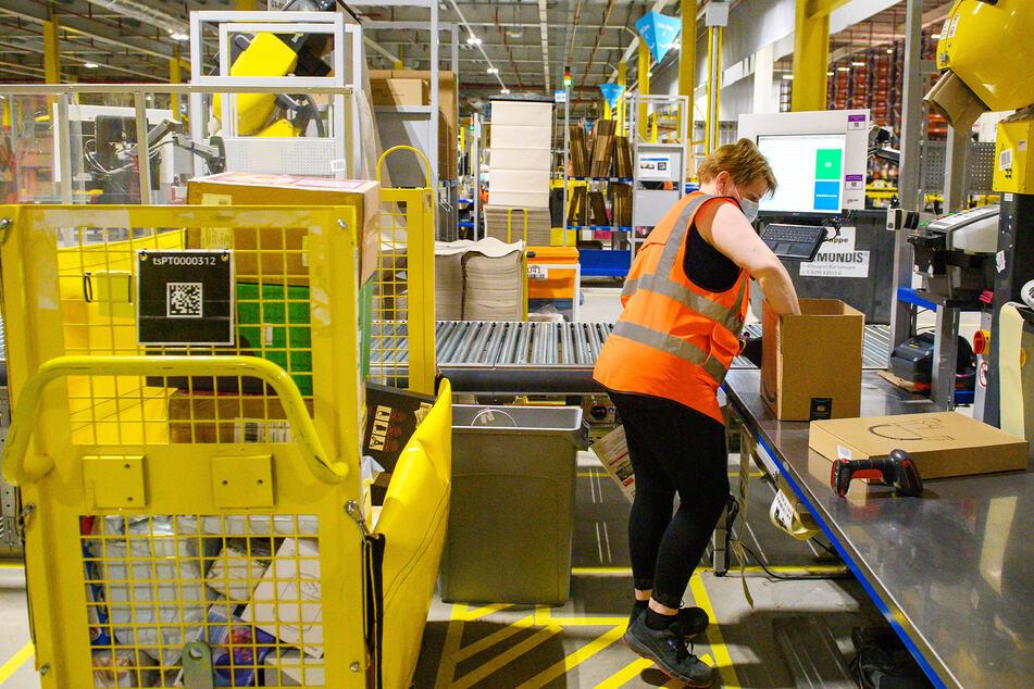 Eine Mitarbeiterin des Amazon Logistikzentrums in Sachsen-Anhalt packt ein Paket (Symbolbild).