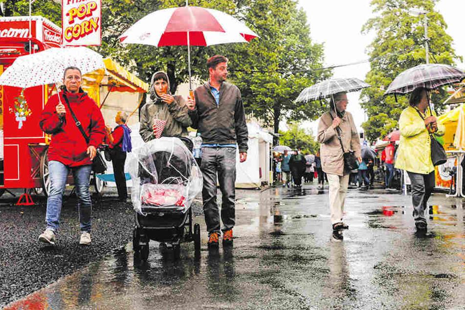 Regenkleidung und Regenschirme sind unabdingbar, um auf dem Volksfest zu bestehen.