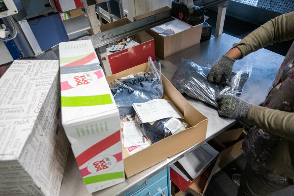 Eine Mitarbeiterin kontrolliert im Rücksendezentrum Pakete mit Retouren. (Archivbild)