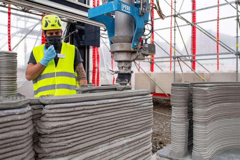 Ein Mitarbeiter des Bauunternehmens beobachtet den 3D Drucker, der die nächste Schicht Beton auf die Wände aufträgt.
