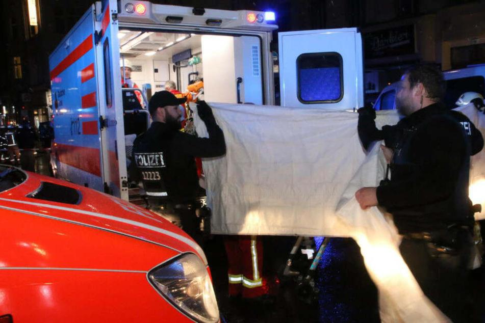 Mit Sichtschutz wird der schwer verletze Mann in den Rettungswagen gebracht.