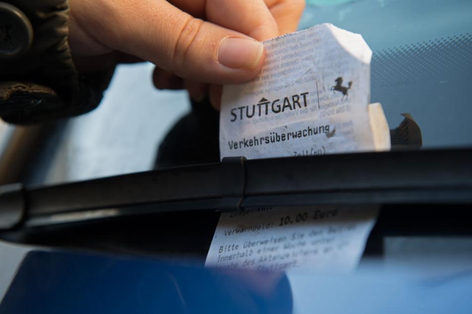 Ein Strafzettel der Verkehrsüberwachung der Stadt steckt am hinter dem Scheibenwischer eines PKWs. (Symbolbild)