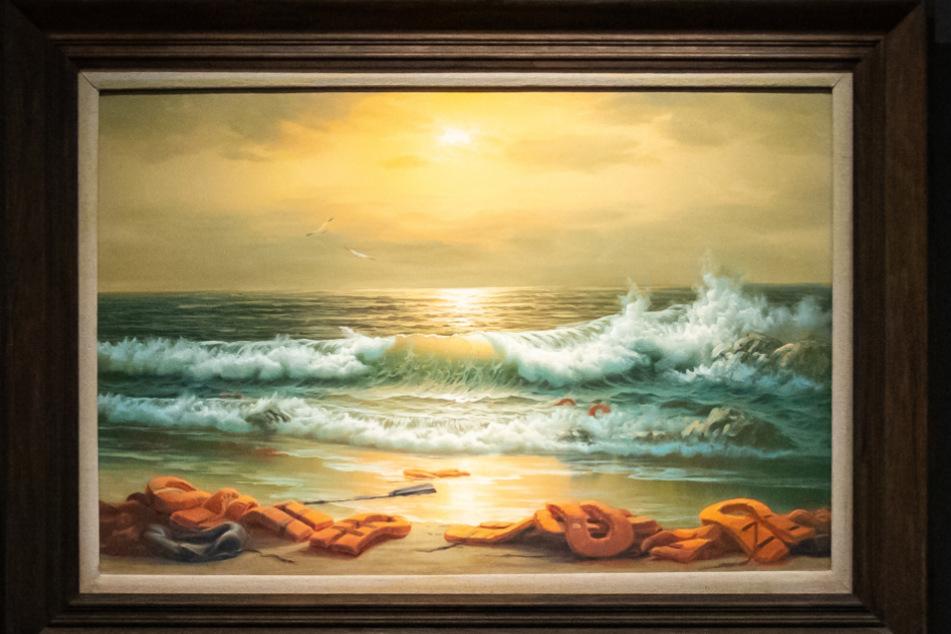 """Ein Gemälde aus dem Triptychon mit dem Namen """"Mediterranean Sea View 2017"""" des britischen Künstlers Banksy hängt im Auktionshaus Sotheby's."""