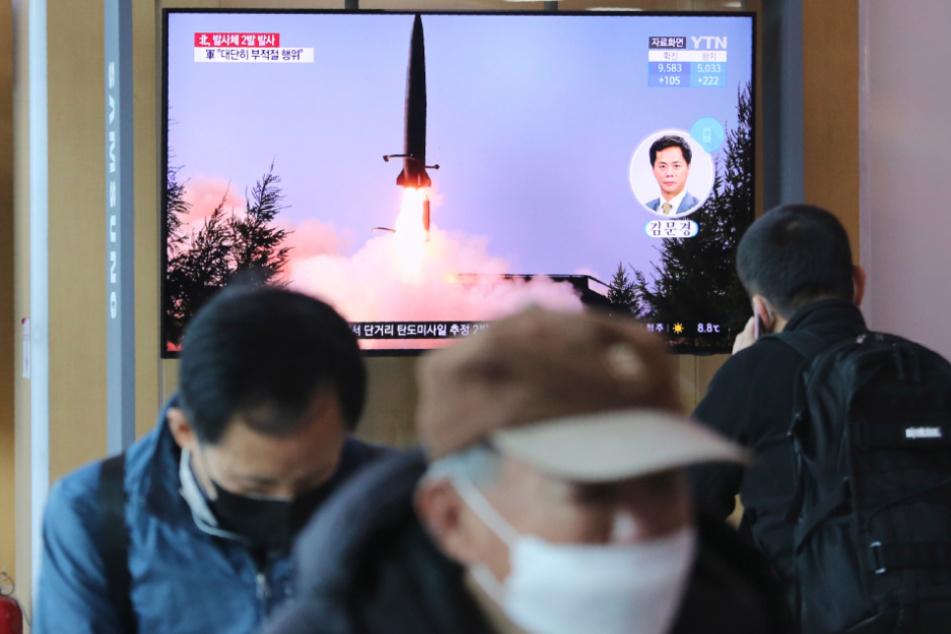 Südkorea, Seoul: Menschen gehen an einem Fernsehbildschirm vorbei, während eine Nachrichtensendung den Start einer Rakete in Nordkorea zeigt.