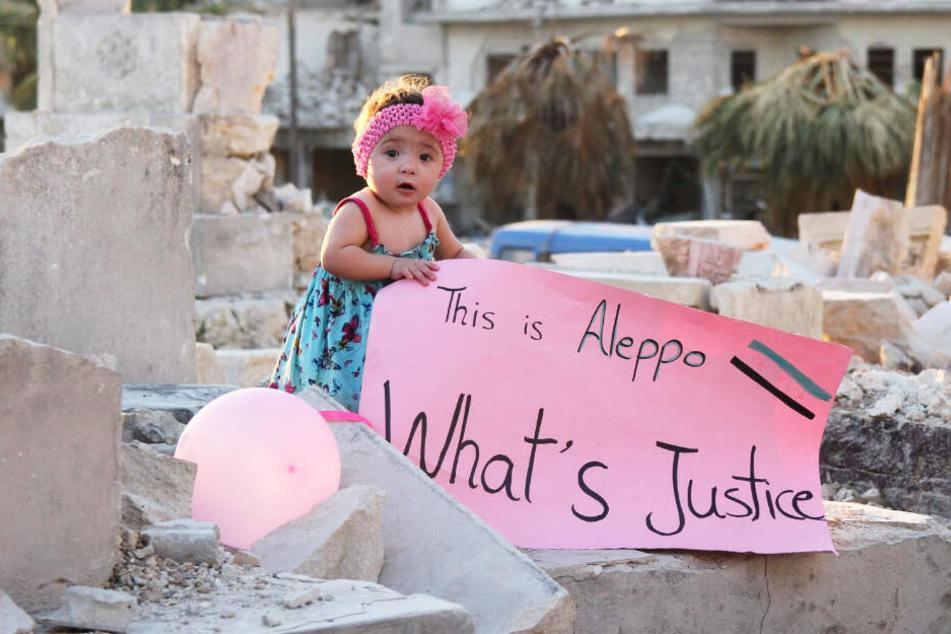 """Sama hält ein Banner mit der Aufschrift: """"Das ist Aleppo. Was ist Gerechtigkeit""""?"""