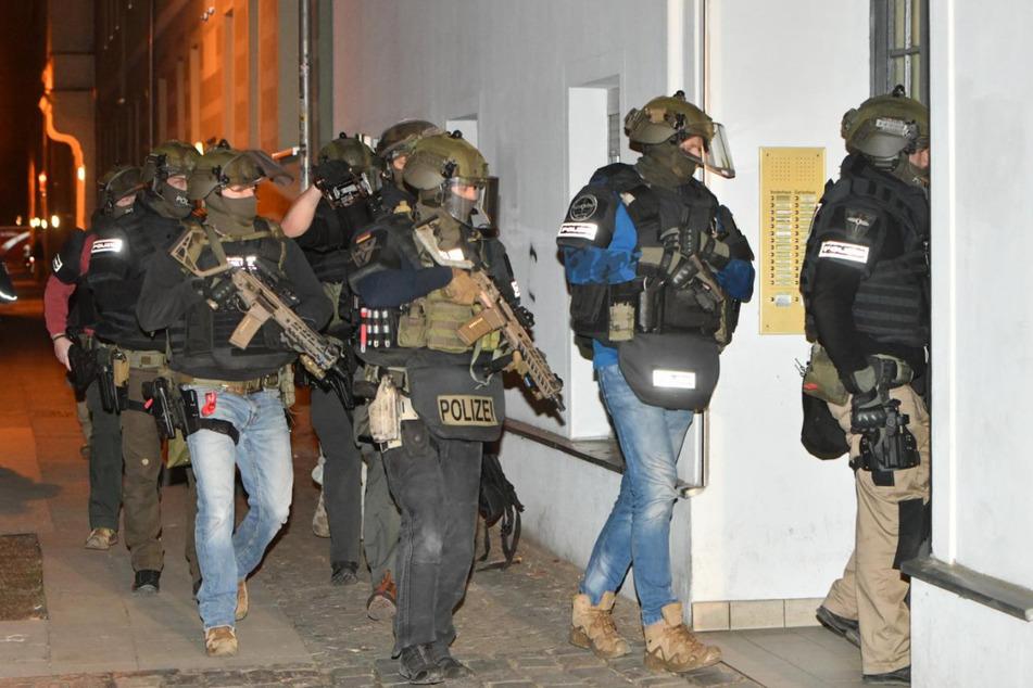 Schwer bewaffnete Polizisten dringen zur Wohnung des Verdächtigen vor.