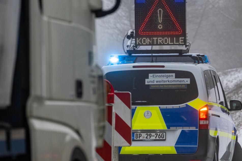 Ein Polizeiwagen kündigt am frühen Morgen eine Kontrolle kurz nach der deutsch-tschechischen Grenze an.
