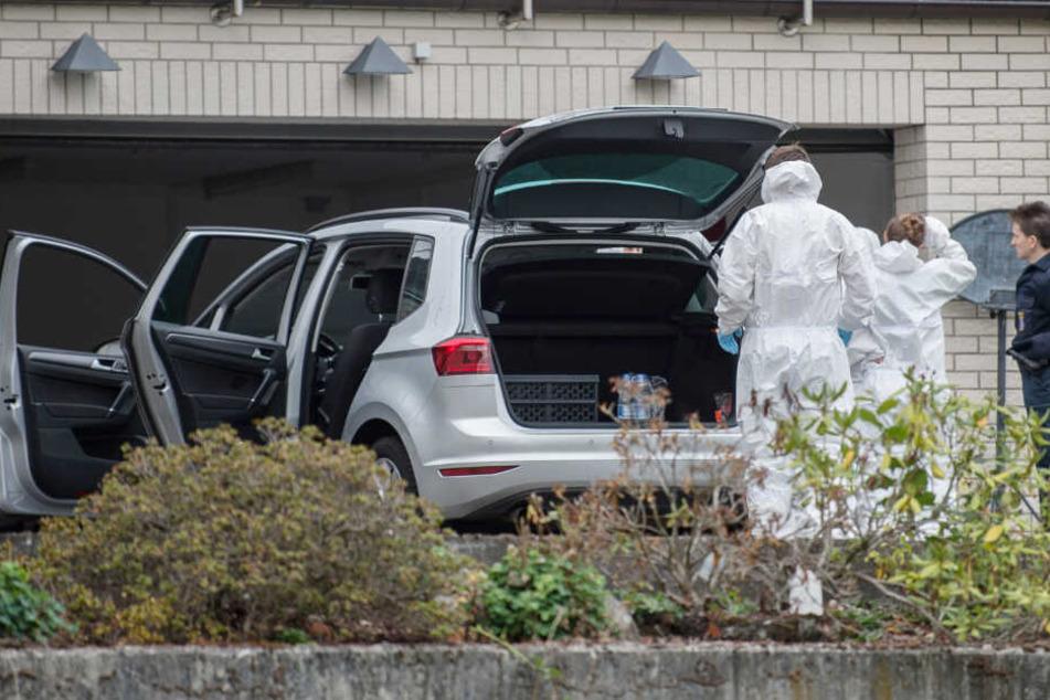 Mitarbeiter der Spurensicherung stehen am 31.08.2018 vor einer Garage am Einfamilienhaus, in dem bei einem Brand zwei tote Kinder geborgen wurden.