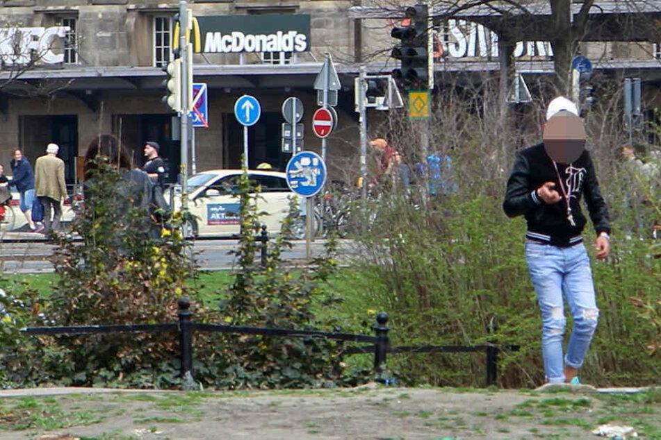 Mit etwas in der Hand verlässt der junge Mann die Rabatte und eilt auf die andere Wegseite zu einem Busch.