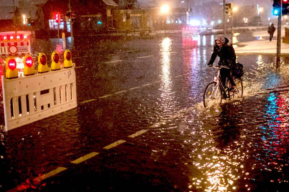 Eine Radlerin fährt in Wismar (Mecklenburg-Vorpommern)  durch das Hochwasser am Stadthafen.