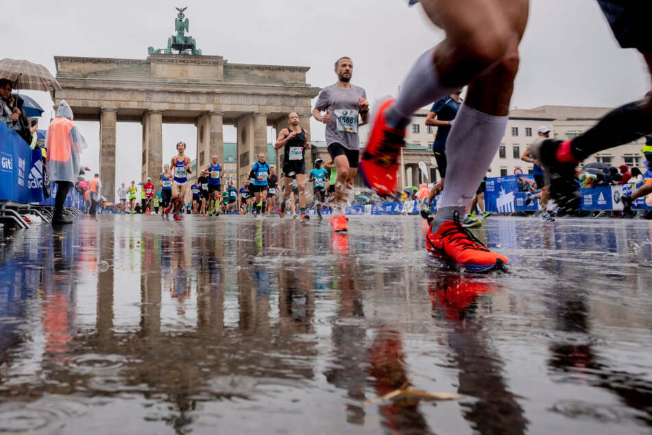 Teilnehmer des 46. Berlin-Marathons laufen bei Regen kurz vor der Ziellinie vor dem Brandenburger Tor.