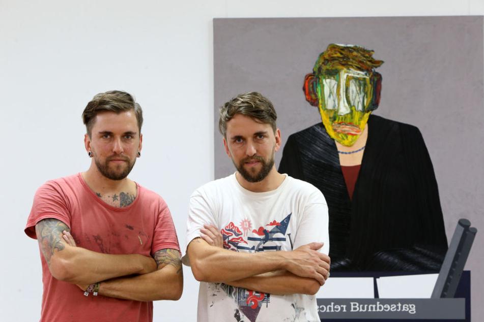 Die Künstler-Zwillinge Marcel (r.) und Robby Oertel (37) aus Kuhschnappel neben einem Gemälde mit einem ihrer Arbeitszombies.