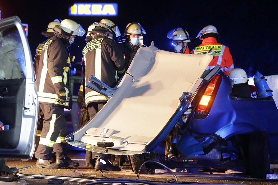 Einsatzkräfte schneiden eine Frau aus ihrem stark demolierten Fahrzeug.