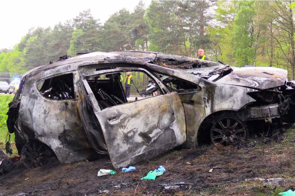 Das verbrannte Auto einer Frau steht nach einem Unfall an der A1. Dabei ist eine 68-Jährige tödlich verletzt worden. Drei weitere Menschen erlitten Verletzungen.