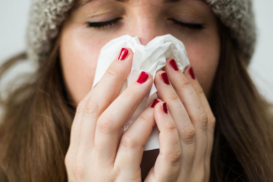 Eine junge Frau, die an der Grippe erkrankt ist. (Symbolbild)