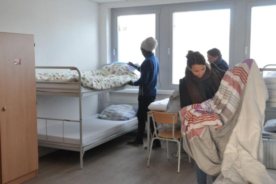 In einer Winternotunterkunft werden die Betten für die Obdachlosen bezogen.