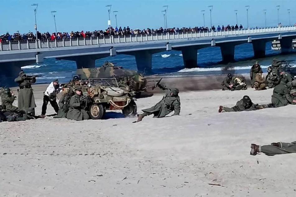 Während im Sand gekämpft wird, drängen sich Schaulustige auf der Seebrücke.