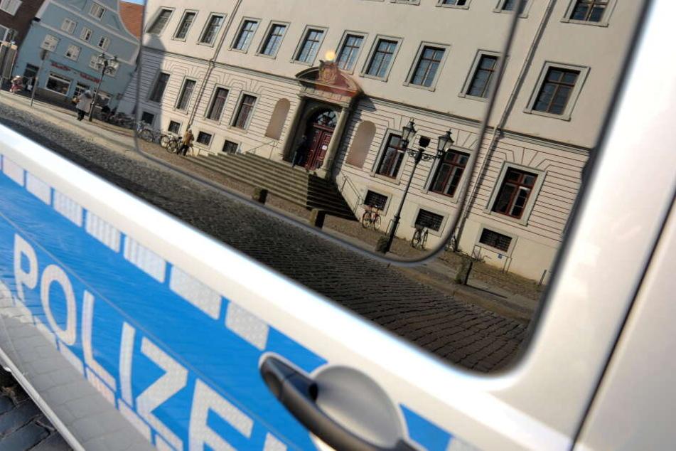 Das Landgericht Lüneburg (Niedersachsen) spiegelt sich in der Scheibe eines Polizeifahrzeuges.