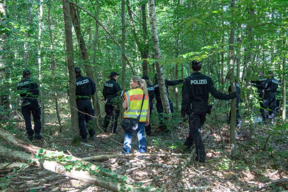 Polizisten suchen in einem Waldstück bei München nach den Leichen der Frau und ihrer Tochter.
