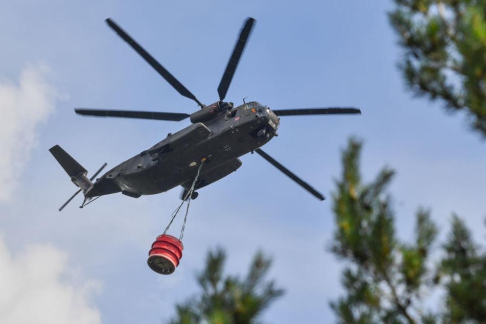 Ein Hubschrauber der Bundeswehr transportiert Löschwasser über dem ehemaligen Truppenübungsplatz in Südbrandenburg.