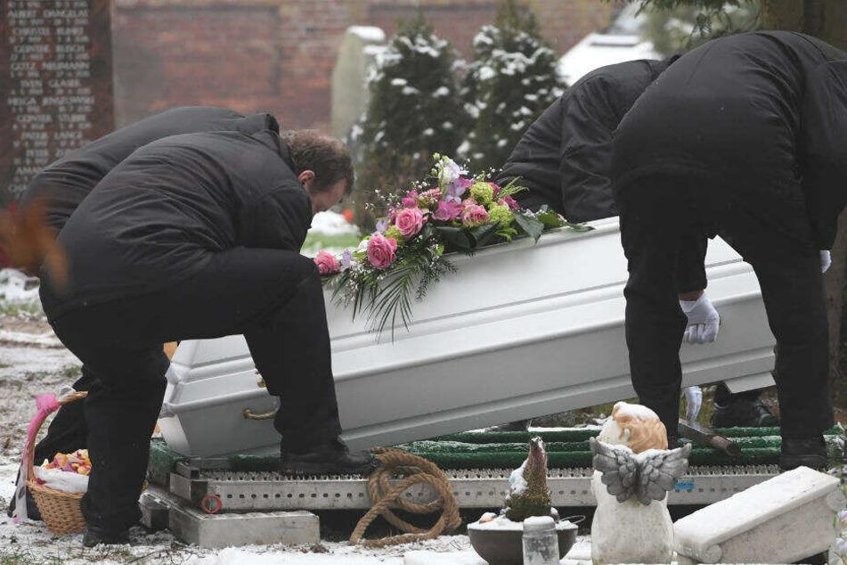 Bestatter senken den Sarg des sechsjährigen Mädchens, das am 12.01.2019 in Torgelow getötet wurde, auf dem Friedhof im Zentrum ins Grab ab.