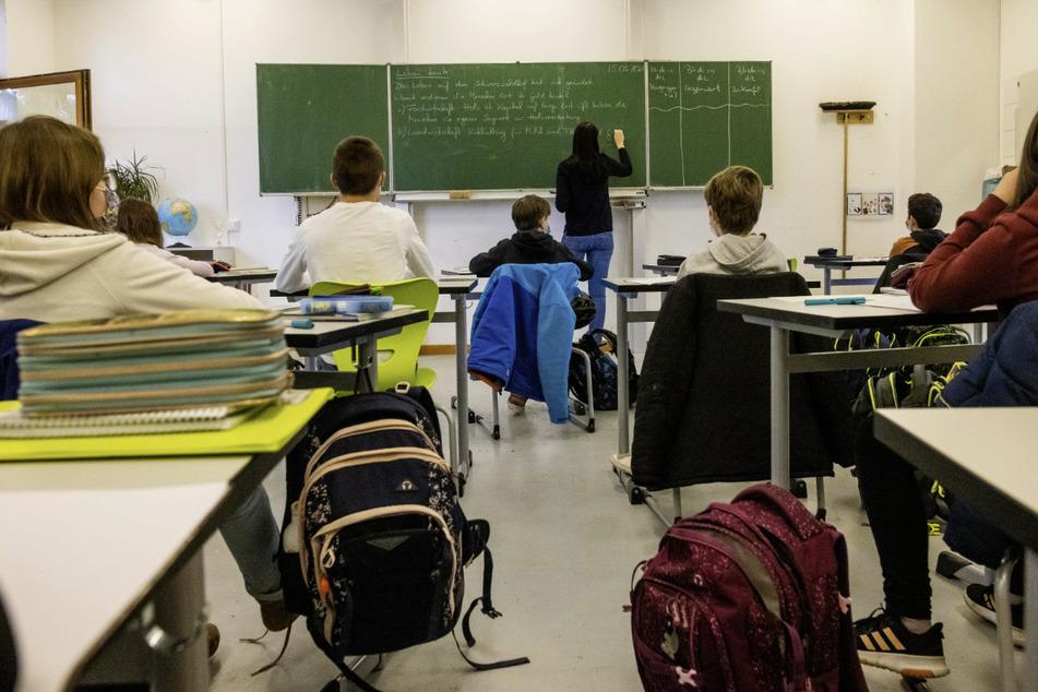 Schülerinnen und Schüler einer fünften Klasse sitzen während des Unterrichts in ihrem Klassenzimmer. (Archivbild)