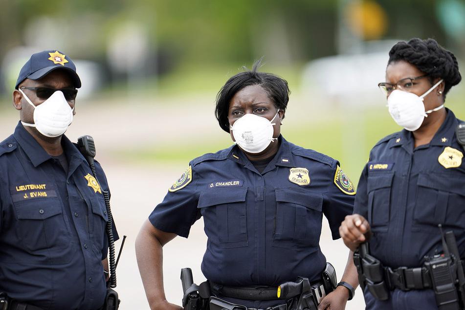 """Polizeibeamte mit Mundschutz patrouillieren an einem neu eröffneten Drive-through des """"United Memorial Medical Center"""", einer Teststation in der sich Bürger kostenlos, meist im Auto sitzend, auf das Coronavirus testen lassen können."""