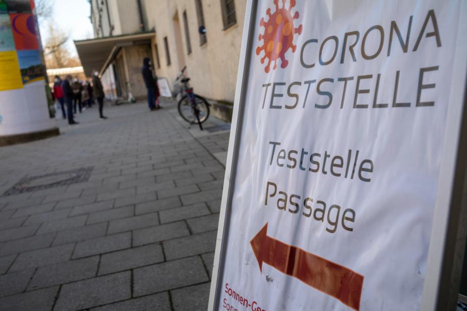 """Ein Schild mit der Aufschrift """"Corona-Teststelle"""" steht vor dem Nebeneingang zum Deutschen Museum."""
