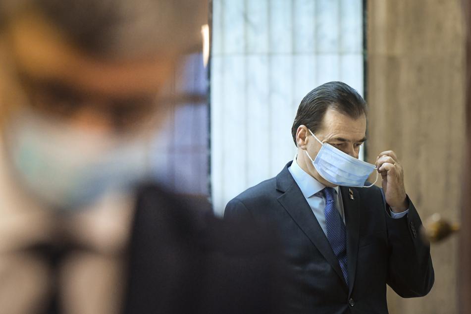 Ludovic Orban, Premierminister von Rumänien, zieht vor einem Treffen der Regierung seinen Mundschutz an. Rumäniens Premierminister musste am Samstag dem 30. Mai 2020 Bußgelder in Höhe von insgesamt rund 600 Dollar zahlen, weil er eine Sitzung in seinem Büro abgehalten hat, bei der er und andere Teilnehmer keinen Mundschutz trugen.