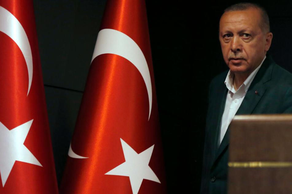 Der türkische Präsident Recep Tayyip Erdogan steht bei einer Pressekonferenz neben Flaggen der Türkei.