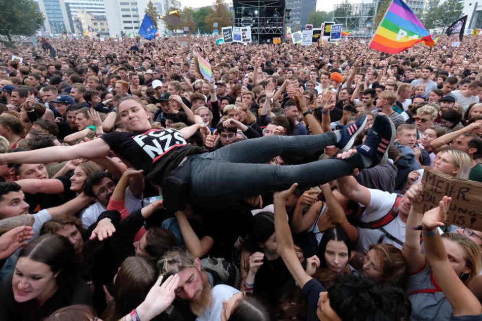 Eine junge Frau lässt sich vom Publikum tragen.