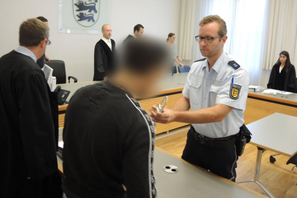 Der Gerichtssaal in Ulm: Dem Angeklagten (vorne) werden vor Beginn der Verhandlung die Handschellen abgenommen.