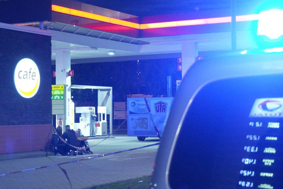 Die Polizei kümmert sich vor der Tankstelle um Zeugen des Raubüberfalls.