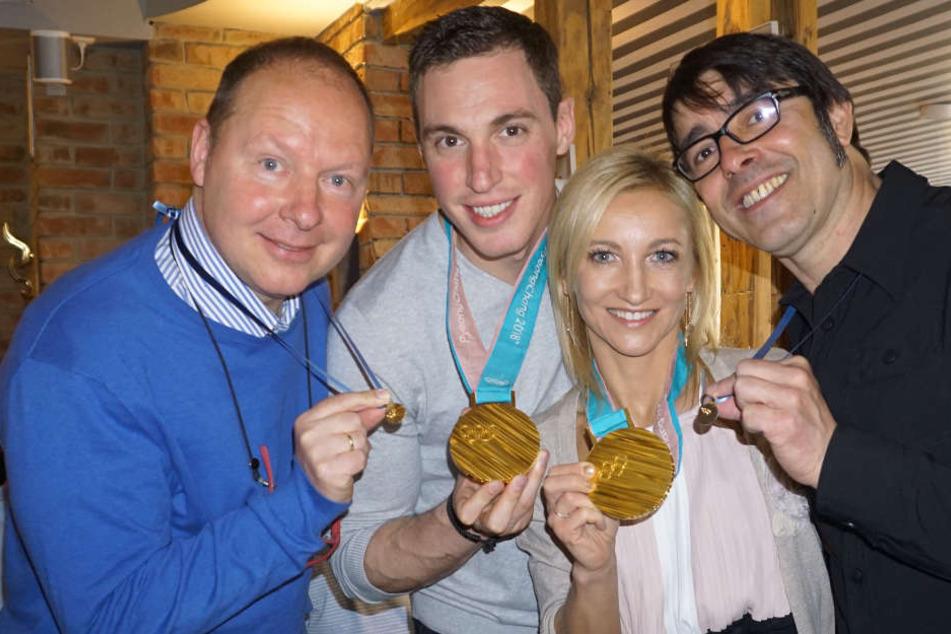 Die Eiskunstläufer Aljona Savchenko und Bruno Massot überreichen im April 2018 ihren Trainern Alexander König (l) und Jean-Francois Ballester (r) extra angefertigte Replikas ihrer olympischen Goldmedaillen.