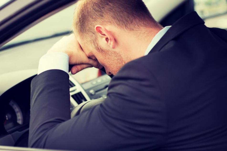 Mann steht mit Wagen auf Autobahn-Ausfahrt und schläft