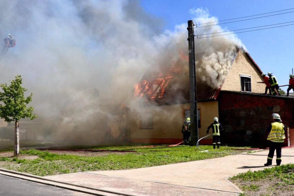 Links und fast komplett eingeraucht ist eine Drehleiter zu sehen. Von beiden Seiten ging die Feuerwehr gegen die Flammen vor.